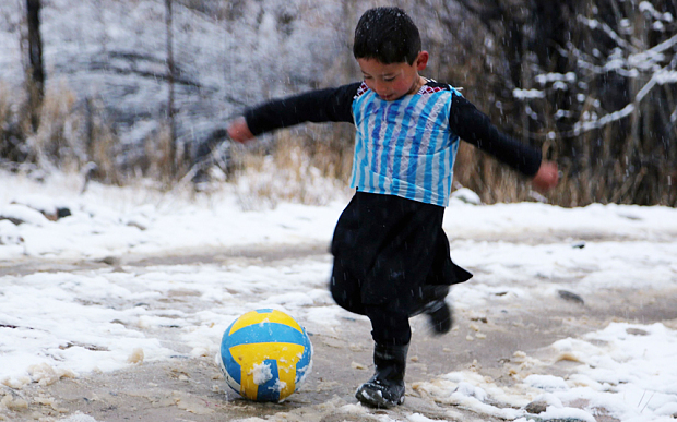 TOPSHOT - In this photograph taken on January 29, 2016, Afghan boy and Lionel Messi fan Murtaza Ahmadi, 5, wears a plastic bag jersey as he plays football in Jaghori district of Ghazni province. A five-year-old Afghan boy has become an internet star after pictures went viral of him wearing an Argentina football shirt made out of a plastic bag, complete with his hero Lionel Messi's name. AFP PHOTO / AFP / STRSTR/AFP/Getty Images
